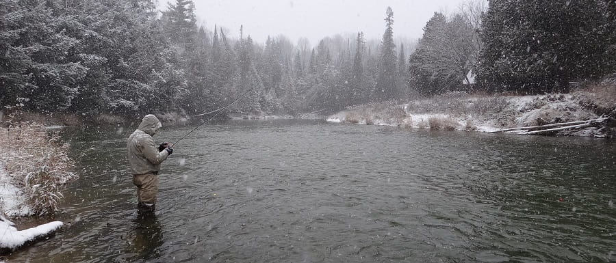 An angler fishing for trout in the winter in Ontario